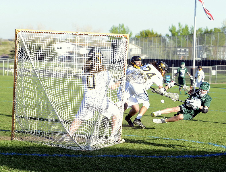 Thompson Valley's Trey Cardenas sends Summit's Aidan Casias flying and without the ball after delivering a blow early during Tuesday's 4A boys lacrosse state playoff game at Patterson Stadium. The No. 2 Eagles rolled to a 21-1 victory. (Mike Brohard/Loveland Reporter-Herald)