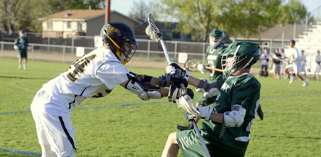 . Thompson Valley\'s Payton Hass dislodges the ball from Summit\'s Andrew Duxbury during Tuesday\'s 4A boys state lacrosse playoff game at Patterson Stadium. The No. 2 Eagles rolled to a victory.