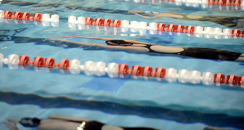 Loveland's Ashley Peet (center) stretches out her underwater at the start of the 100-yard breaststroke during Friday's 4A State Swimming & Diving Finals at Veterans Memorial Aquatic Center in Thornton. (Mike Brohard/Loveland Reporter-Herald)