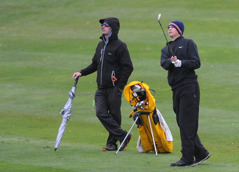 Thompson Valley coach Derek Shagin, left, and senior Darren Edwards watch his approach shot on the ninth hole during the first round of the 4A state golf tournament on Monday at Raccoon Creek in Littleton.