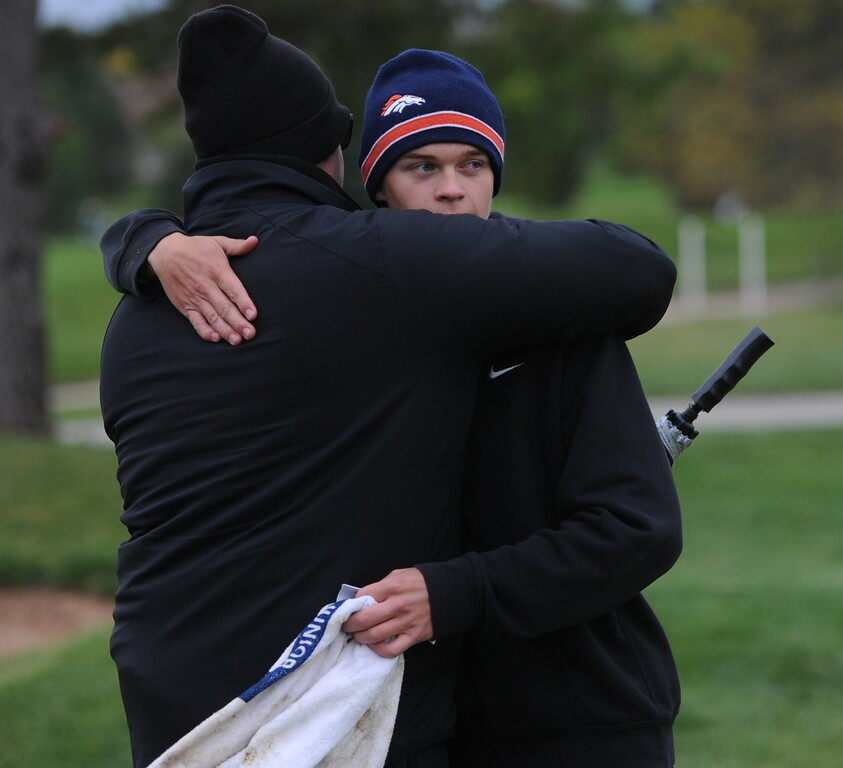 Thompson Valley senior Darren Edwards gives his dad a hug after finishing the first round of the 4A state golf tournament on Monday at Raccoon Creek in Littleton.