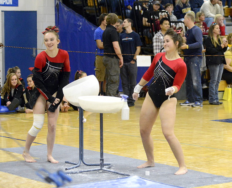 Loveland's Hallie Lunsford, left, and Cadi Salza dance along to the floor music in the background as they get ready to compete on the uneven bars during Friday's 4A State Gymnastics meet at Thornton High School.