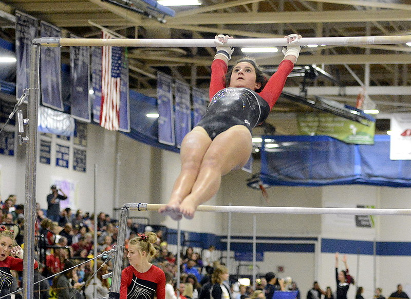Loveland's Olivia Mascio competes on the uneven bars Friday at the 4A State Gymnastics meet at Thornton High School.