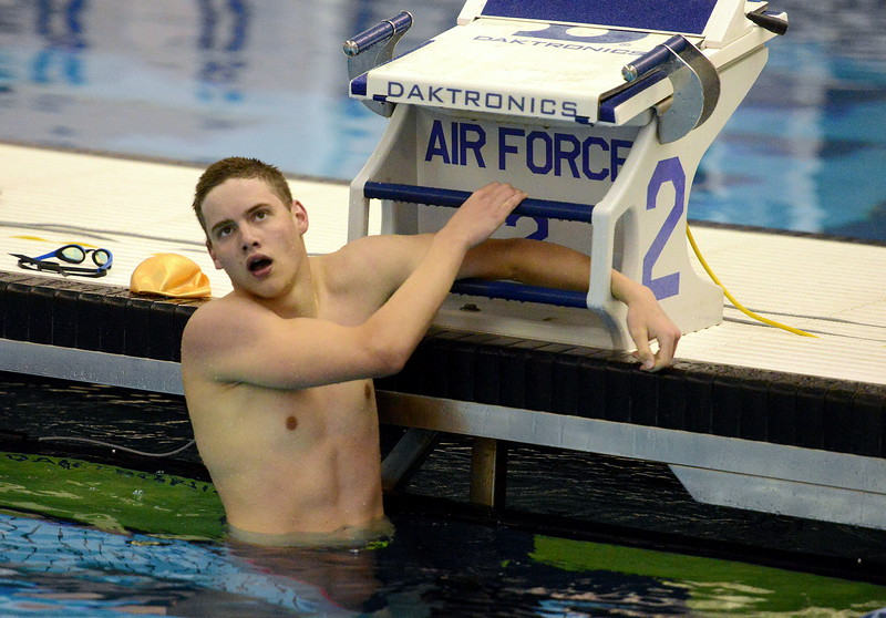 Josh Dodrill of Windsor holds on the blocks as he looks at the board at the end of the 100-yard butterfly finals  at the 4A state boys swim and dive meet Saturday at the Air Force Academy Natatorium. (Mike Brohard/Loveland Reporter-Herald)