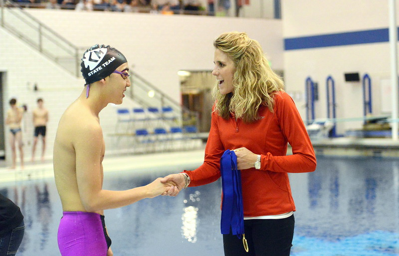 Kenzie Hewson of CHSAA shakes hands with unified swimmer Andrew Yi after he won the second heat at the 4A state boys swim and dive meet Saturday at the Air Force Academy Natatorium. (Mike Brohard/Loveland Reporter-Herald)