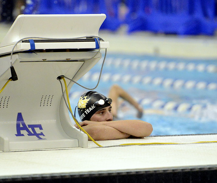 Thompson Valley's Michael Vierra peaks over the bulkhead during warmup to watch a teammate dive Friday at the Air Force Academy Natatorium. (Mike Brohard/Loveland Reporter-Herald)