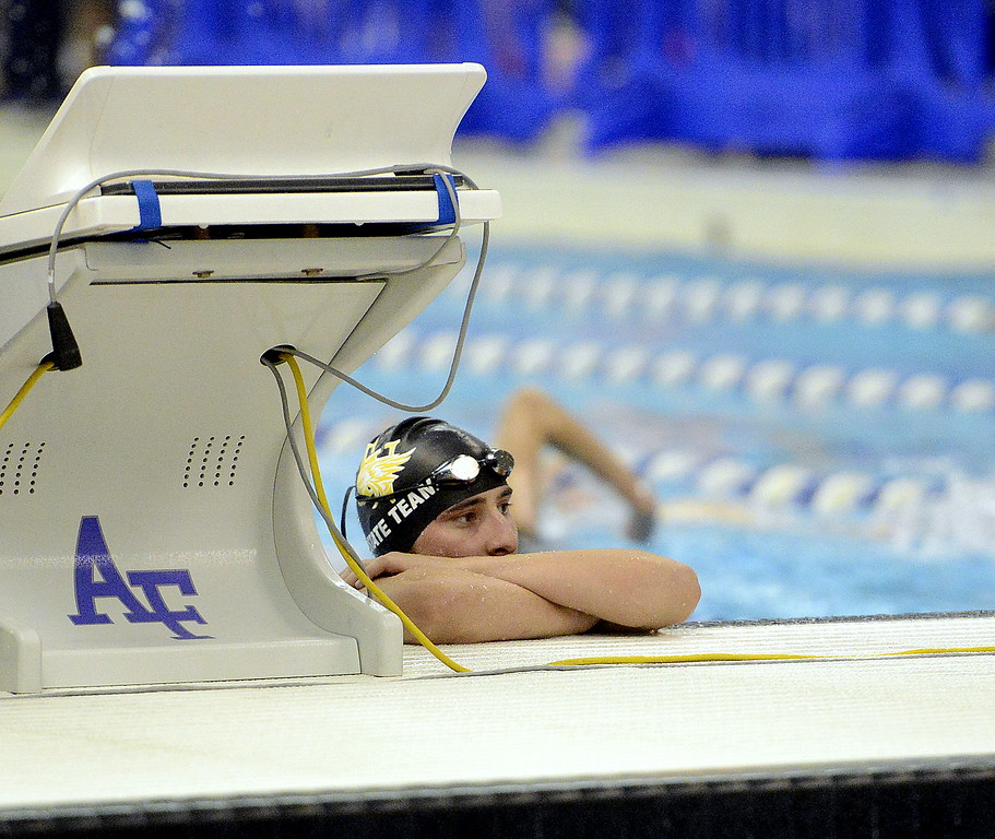 . Thompson Valley\'s Michael Vierra peaks over the bulkhead during warmup to watch a teammate dive Friday at the Air Force Academy Natatorium. (Mike Brohard/Loveland Reporter-Herald)