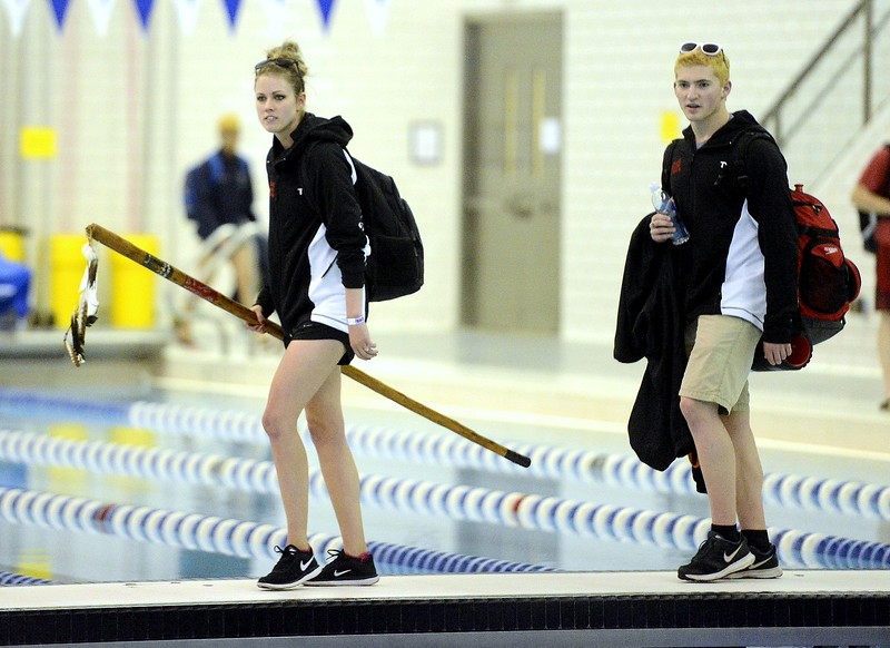 Loveland coach Sarah Vlatkovich enters the Air Force Academy Natatorium  with the spirit stick as senior Deven Gogarty follows behind. (Mike Brohard/Loveland Reporter-Herald)