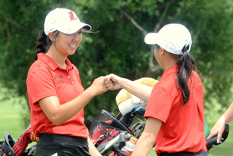 Loveland's Natalee Hall (left) and Casey Bradley pop knuckles on the eighth tee box during the first round of the 4A state girls golf tournament Monday at Country Club of Colorado in Colorado Springs (Mike Brohard/Loveland Reporter-Herald)