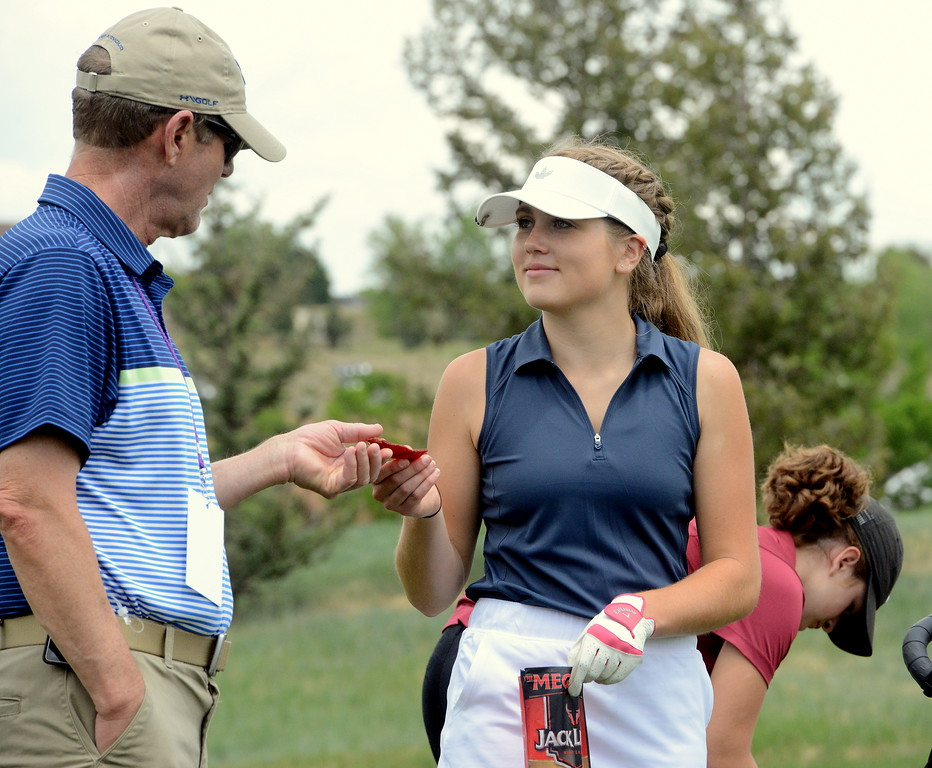 Renee Demaree of Mountain View shares some beef jerkey with assistant coach John Perry during the first round of the 4A state girls golf tournament Monday at Country Club of Colorado in Colorado Springs (Mike Brohard/Loveland Reporter-Herald)