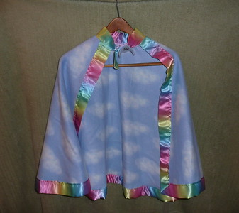 #4 - Blue cloud material with rainbow ribbon trim - $15 or two for $25  (All capes are fleece and have velcro closure at the neck)