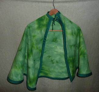 #3 - Green tie-dye with green trip.  Closure decoration is a Christmas holly leaf - $15 or two for $25  (All capes are fleece and have velcro closure at the neck)