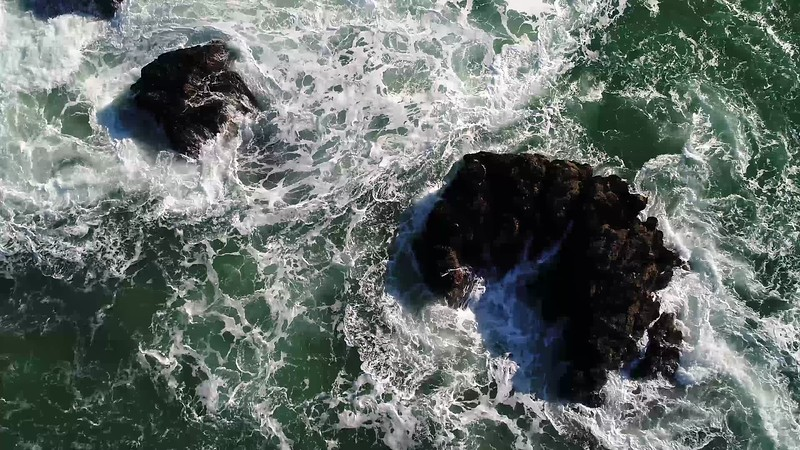 God's Eye View of Ocean Rocks with Swirling Ocean Water & Waves
