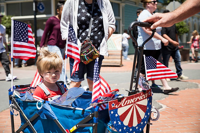 Mason Allen-Cook sits in his cart while being pulled by his dad during the Fourth of July celebrations in Old Town Eureka on Tuesday. (Sam Armanino - The Times-Standard)