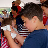 Nine year old Domenic Coakley looks at his prize after winning the 10 and under pie eating contest at the Livingston Street Recreation Center in Tewksbury during the annual 4t of July events. (The Sun Chris Tierney)