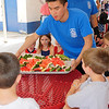 Tewksbury Community Services employee Dennis Ong places down a tray of watermelon for the ten and under watermelon eating contest. Kids had one minute to eat as many slices as possible at the Livingston Street Recreation Center. (The Sun / Chris Tierney)