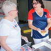 Janice Higgins and Doreen Muroney serve hot dogs at the Livingston Street Recreation Center for the 4th of July events. (The Sun / Chris Tierney)
