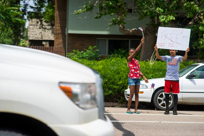 Aliyah Dodd, left, and Isaih Dodd hold up a sign to passing cars advertising their free hot dogs their father, Joe Dodd, is cooking up on July 4, 2016 on the corner of 22nd Street and Firstview Drive. Dodd's children wake up excited for the free hot dogs every July 4.<br /> <br /> Photo by Michael Ortz/ Loveland Reporter-Herald