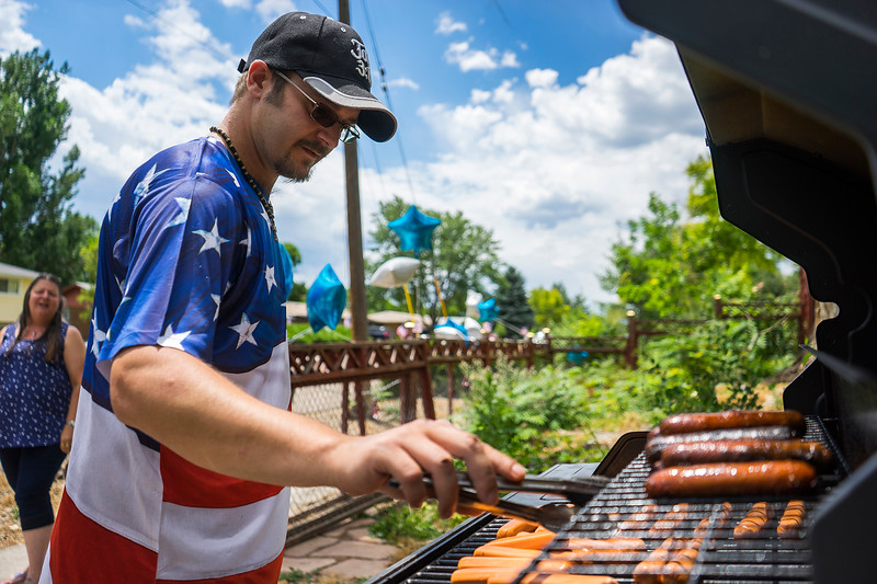 """Joe Dodd cooks his famous """"freedom dogs"""" in his backyard on the corner of 22nd Street and Firstview Drive on July 4, 2016. Dodd has been cooking hot dogs for the public on July 4 for the past 5 years.<br /> <br /> Photo by Michael Ortiz/ Loveland Reporter-Herald"""