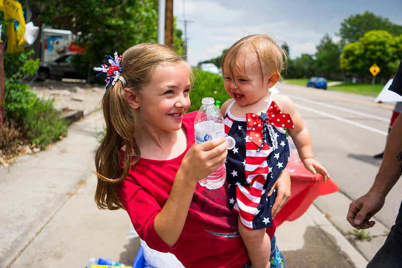 Natalee Premus, 9, and her sister Emalee Premus stop at Joe Dodd's house on 22nd Street and Firstview Drive with their father for a hot dog and water on July 4, 2016. The Premus family are neighbors with Dodd and had no idea he gave out free hot dogs until they saw all the balloons and decided to visit.<br /> <br /> Photo by Michael Ortiz/ Loveland Reporter-Herald