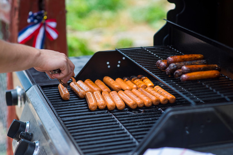 """Joe Dodd cooks hot dogs in anticipation of a busy night on July 4, 2016 in his backyard on the corner of 22nd and Firstview Drive. Dodd started cooking his """"freedom dogs"""" after the """"freedom fries"""" movement in 2003.<br /> <br /> Photo by Michael Ortiz/ Lvoeland Reporter-Herald"""