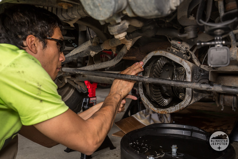 Steve Baskis scraping RTV from the front differential of his 2003 Jeep Wrangler Rubicon.