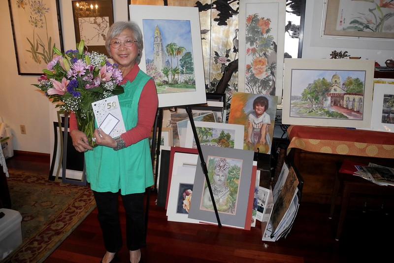 Standing in the Living Room with many off Kitty's recent Paintings.<br /> The center Portrait is Granddaughter Mia.