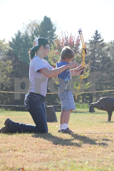 Seen here is (left to right): Morgan Hansen assisting Ryan Davis in  the use of  bow and arrow, just one of many  activities for families attending the 50th  Celebration for Kennedy Park and Trail held on Sunday, October 11, 2015. The event took place at  Kennedy Park in Fort Dodge.