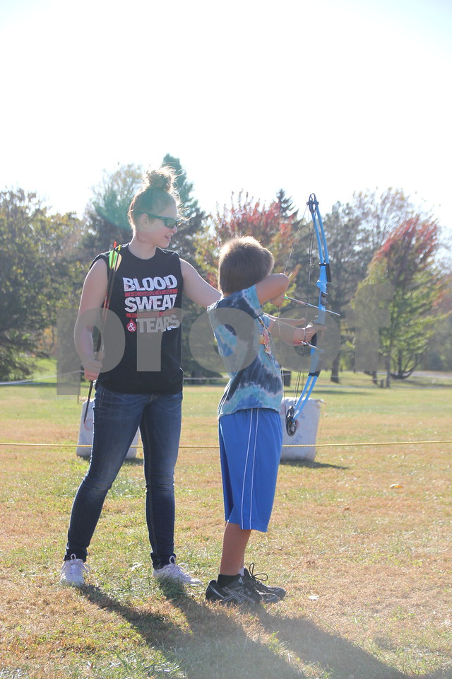 Seen here is (left to right): Taylor Hammersland assisting a young boy (name unknown) in the use of bow and arrow, just one of many activities for families attending the 50th Celebration for Kennedy Park and Trail held on Sunday, October 11, 2015. The event took place at Kennedy Park in Fort Dodge.