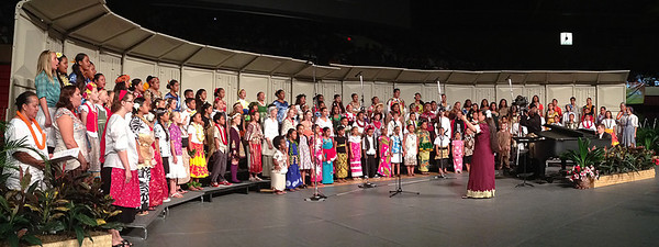 "PCC alumna Esther Dela Rosa Macy leads her Koolauloa Children's Chorus — consisting primarily of the children of grandchildren of other PCC alumni, who all dressed in traditional ethnic attire — in the theme song of the Polynesian Cultural Center's 50th Anniversary, ""Voyage of Faith,"" with lyrics by PCC alumna and former vice president Vernice Wineera (Dan Bradshaw, accompanist) . . . in the PCC's Musical Fireside on September 1, 2013, in the BYU-Hawaii Cannon Activities Center. (Polynesian Cultural Center photo by Mike Foley)"