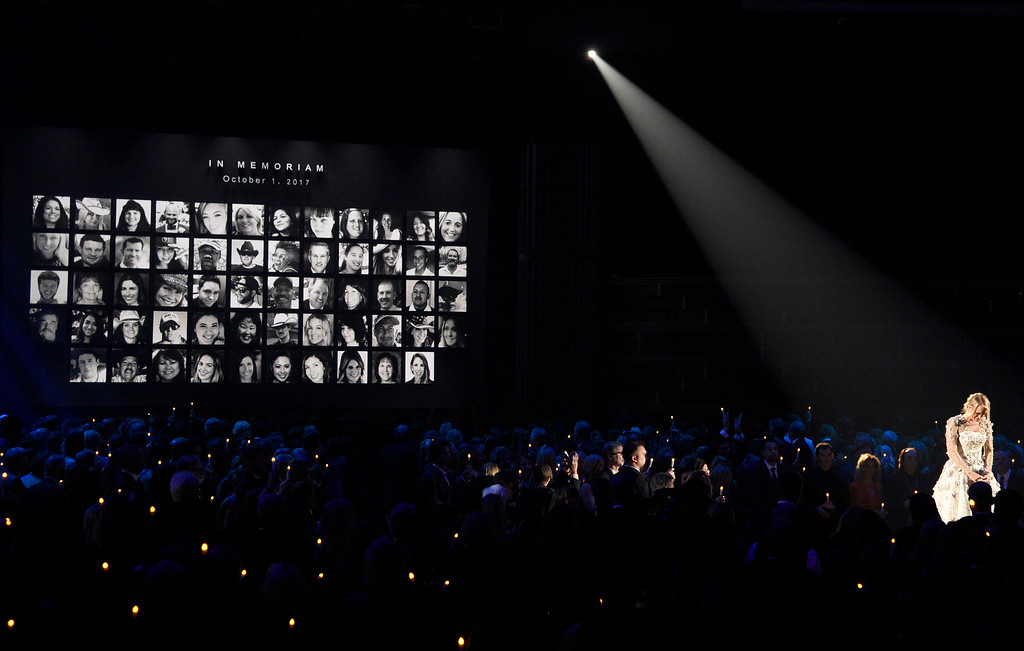 ". Carrie Underwood pauses during a performance of ""Softly and Tenderly\"" during an In Memoriam tribute at the 51st annual CMA Awards at the Bridgestone Arena on Wednesday, Nov. 8, 2017, in Nashville, Tenn. Pictured on screen are victims of the Route 91 Harvest mass shooting. (Photo by Chris Pizzello/Invision/AP)"