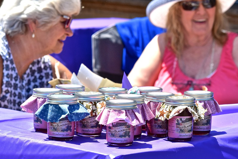 Glenda Howard and Margie Jackman sit behind all that is left of the jams made by the Westhaven Ladies Club. Blackberry jam ran out early on, with their remaining homemade strawberry jam quickly being scooped up as well. José Quezada—For the Times-Standard