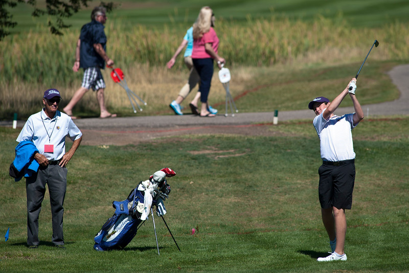 Photo by William Woody -- Freddie Gluck of Boulder hits from the rough with coach Rick Uhlir looking on, on the par-five 18th hole at Bookcliff Country Club Monday morning, Sept. 26, 2016, in Grand Junction Colo.
