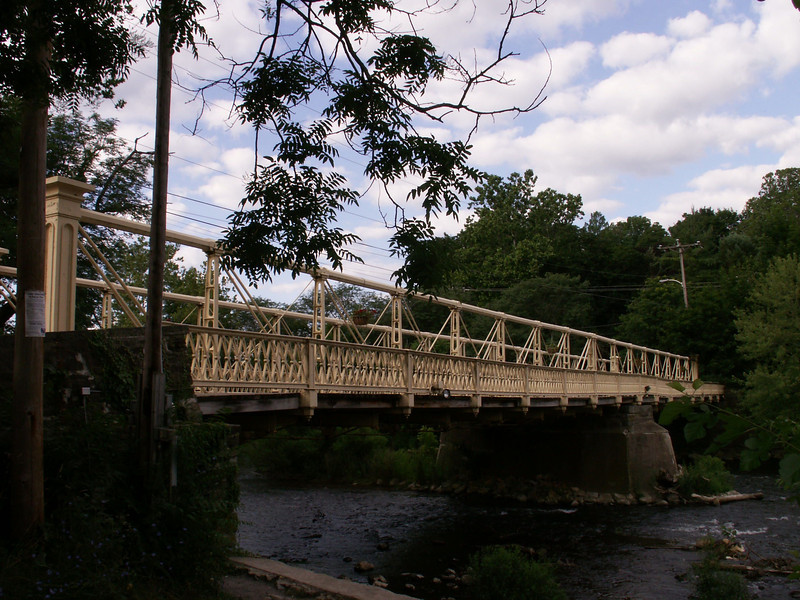 "<a href=""http://www.historicbridges.org/"">Photo Courtesy of Nathan Holth with Historicbridges.org</a>  The 140 year-old Hunterdon County Bridge is still in use thanks to a $340,000 TE award for its restoration. Farmers, traveling with horse drawn carts, used this bridge over the south branch of the Raritan River when they came to market to sell their goods and purchase supplies. Over the years the bridge fell into disrepair, trusses were bent or broken, bolt hangers, and the stone masonry began to deteriorate. Maintenance was done on an emergency basis or deferred; bridge inspectors noted the structure's historic significance while recommending that the whole structure be replaced. Due to the historic significance of the bridge and public support, the county opted to rehabilitate the bridge. Rehabilitating the bridge proved to be the best decision all around: it was less expensive than replacing the bridge, it would require less closure time and not affect bike, pedestrian, or canoe travel on the river below, and its historic elements made it eligible for TE funding. The restored Hunterdon County Bridge not only connects Main Street businesses with a historic mill and museum, but it also provides the community with a link to its past while they travel to their future."