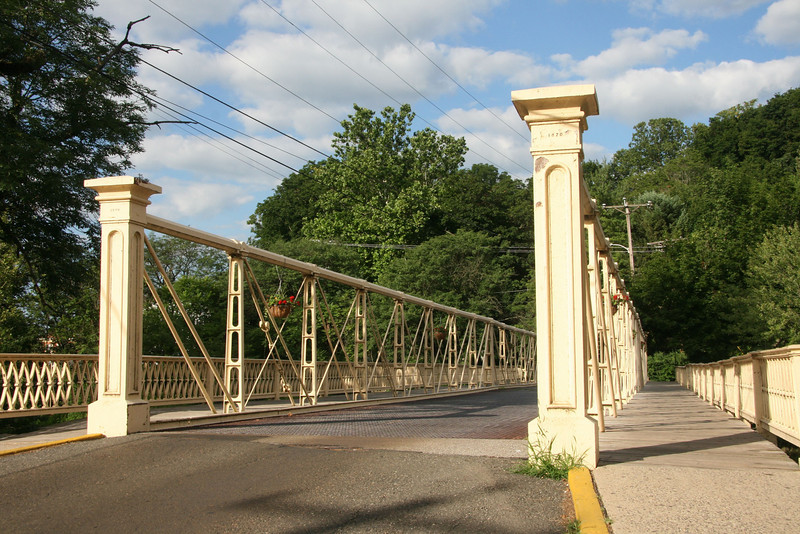 "<a href=""http://www.historicbridges.org/"">Photo Courtesy of Rick McOmber with Historicbridges.org</a>  The 140 year-old Hunterdon County Bridge is still in use thanks to a $340,000 TE award for its restoration. Farmers, traveling with horse drawn carts, used this bridge over the south branch of the Raritan River when they came to market to sell their goods and purchase supplies. Over the years the bridge fell into disrepair, trusses were bent or broken, bolt hangers, and the stone masonry began to deteriorate. Maintenance was done on an emergency basis or deferred; bridge inspectors noted the structure's historic significance while recommending that the whole structure be replaced. Due to the historic significance of the bridge and public support, the county opted to rehabilitate the bridge. Rehabilitating the bridge proved to be the best decision all around: it was less expensive than replacing the bridge, it would require less closure time and not affect bike, pedestrian, or canoe travel on the river below, and its historic elements made it eligible for TE funding. The restored Hunterdon County Bridge not only connects Main Street businesses with a historic mill and museum, but it also provides the community with a link to its past while they travel to their future."