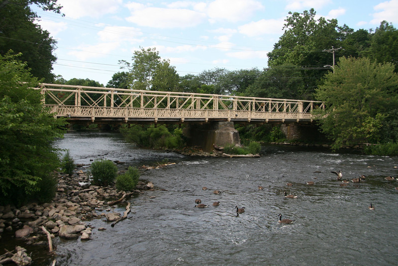 """<a href=""""http://www.historicbridges.org/"""">Photo Courtesy of Nathan Holth with Historicbridges.org</a>  The 140 year-old Hunterdon County Bridge is still in use thanks to a $340,000 TE award for its restoration. Farmers, traveling with horse drawn carts, used this bridge over the south branch of the Raritan River when they came to market to sell their goods and purchase supplies. Over the years the bridge fell into disrepair, trusses were bent or broken, bolt hangers, and the stone masonry began to deteriorate. Maintenance was done on an emergency basis or deferred; bridge inspectors noted the structure's historic significance while recommending that the whole structure be replaced. Due to the historic significance of the bridge and public support, the county opted to rehabilitate the bridge. Rehabilitating the bridge proved to be the best decision all around: it was less expensive than replacing the bridge, it would require less closure time and not affect bike, pedestrian, or canoe travel on the river below, and its historic elements made it eligible for TE funding. The restored Hunterdon County Bridge not only connects Main Street businesses with a historic mill and museum, but it also provides the community with a link to its past while they travel to their future."""
