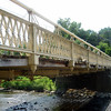 """<a href=""""http://www.flickr.com/people/wallyg/"""">Photo Credit</a>  The 140 year-old Hunterdon County Bridge is still in use thanks to a $340,000 TE award for its restoration. Farmers, traveling with horse drawn carts, used this bridge over the south branch of the Raritan River when they came to market to sell their goods and purchase supplies. Over the years the bridge fell into disrepair, trusses were bent or broken, bolt hangers, and the stone masonry began to deteriorate. Maintenance was done on an emergency basis or deferred; bridge inspectors noted the structure's historic significance while recommending that the whole structure be replaced. Due to the historic significance of the bridge and public support, the county opted to rehabilitate the bridge. Rehabilitating the bridge proved to be the best decision all around: it was less expensive than replacing the bridge, it would require less closure time and not affect bike, pedestrian, or canoe travel on the river below, and its historic elements made it eligible for TE funding. The restored Hunterdon County Bridge not only connects Main Street businesses with a historic mill and museum, but it also provides the community with a link to its past while they travel to their future."""
