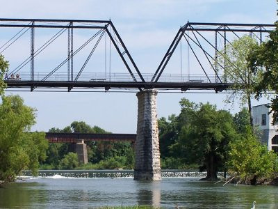 """This category 7 project rehabilitated the historic Faust Street Bridge in New Braunfels, TX. The bridge was originally built by the King Bridge Company of Cleveland, Ohio in 1887 to span the Guadalupe River. The construction of the bridge was funded by Comal County with an initial price tag of $33,269. It is the only multiple-span Whipple Truss Bridge in the state of Texas that resides at its original site.  In 1978, as a result of a fire, the bridge was closed to traffic. Thanks to $360,000 in Transportation Enhancements funding and a local match of $72,000 in 1994 the bridge is still here today. The category 7 project rehabilitated the bridge so that it could be used to carry pedestrians and bicyclists across the Guadalupe River. The rehabilitation was carried out by the <a href=""""http://www.sparksengineering.com/"""">Sparks Engineering, Inc.</a> who also worked on the nearby <a href=""""http://www.images.enhancements.org/7-Rehab-Hist-Transp-Facilities/Hays-Street-Bridge/"""">Hays Street Bridge</a>  in San Antonio.   Visit the <a href=""""http://historicbridgefoundation.com/txbridges/hillcountry/comal/faust.html """">Historic Bridge Foundation </a> for more information on the bridge."""