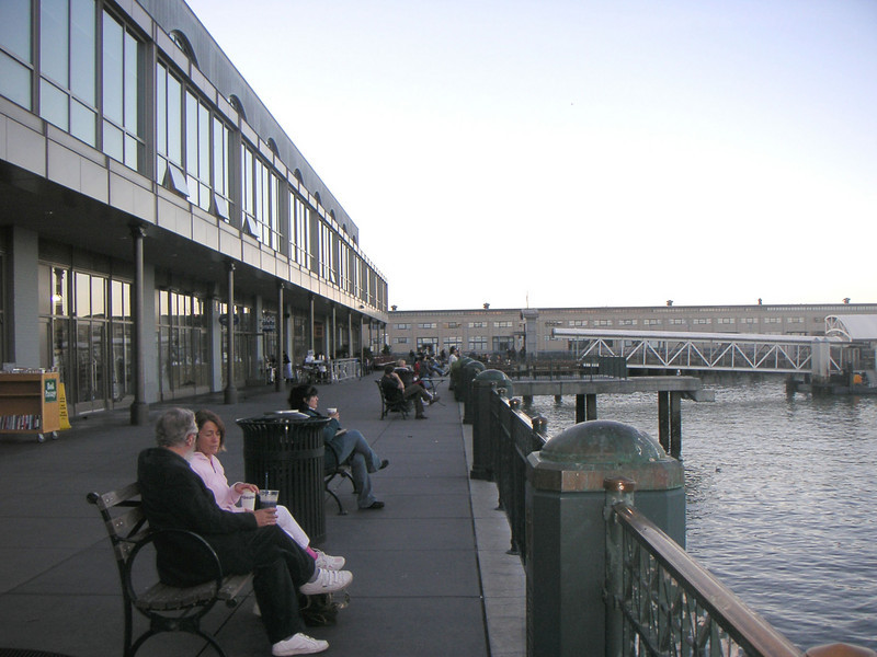 """The back side of the Ferry Building is just as beautiful as the front. Benches and picnic tables encourage visitors to stay and enjoy the awesome view of the San Francisco Bay.  The <a href=""""http://www.ferrybuildingmarketplace.com/"""">Ferry Building</a>, built in 1898, has survived two major earthquakes and is listed in the National Register of Historic Places. Though it is now a major inter-modal transportation center and mixed-use complex, it has not always been so. Until the opening of the Bay and Golden Gate Bridges in 1936 and 1937, respectively, the Ferry Building was the focal point of ferry and rail transportation. When auto travel became the dominant mode for traveling across the Bay, the Ferry Building became obsolete and was transformed into primarily office use. To make matters worse, the elevated Embarcadero Freeway was built directly in front of the building in 1957 cutting the building off from the rest of downtown. The 1989 Loma Prieta Earthquake instigated the redevelopment of the Embarcadero and the Ferry Building when it destroyed part of the elevated freeway.    Two TE awards, procured in 1995 and 1998, were used to complete the Ferry Building Rehabilitation project. In total, State TE funding amounted to $2 million and generated a total local match of $2,201,000. Today, visitors and commuters from East Bay and Marin County can connect to downtown San Francisco via passenger ferries, light rail, the subway system, historic streetcars, cable cars, and buses. In addition, the Ferry Building is now truly mixed-use with retail shops, restaurants, food markets, conference center, and office space fill its historic space."""