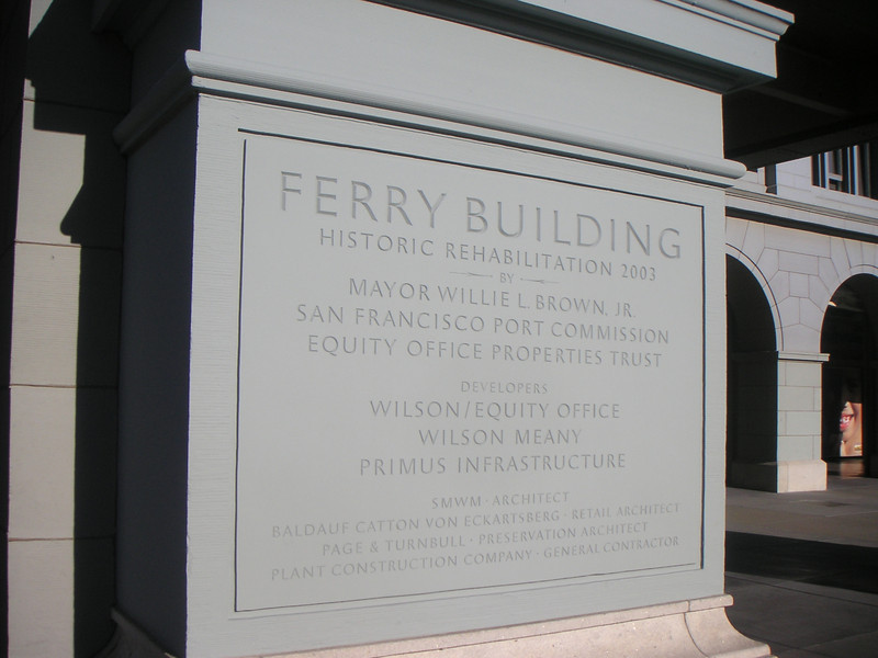 "This placard on the face of the Ferry Building marks the completion of this historic building's rehabilitation in 2003.   The <a href=""http://www.ferrybuildingmarketplace.com/"">Ferry Building</a>, built in 1898, has survived two major earthquakes and is listed in the National Register of Historic Places. Though it is now a major inter-modal transportation center and mixed-use complex, it has not always been so. Until the opening of the Bay and Golden Gate Bridges in 1936 and 1937, respectively, the Ferry Building was the focal point of ferry and rail transportation. When auto travel became the dominant mode for traveling across the Bay, the Ferry Building became obsolete and was transformed into primarily office use. To make matters worse, the elevated Embarcadero Freeway was built directly in front of the building in 1957 cutting the building off from the rest of downtown. The 1989 Loma Prieta Earthquake instigated the redevelopment of the Embarcadero and the Ferry Building when it destroyed part of the elevated freeway.    Two TE awards, procured in 1995 and 1998, were used to complete the Ferry Building Rehabilitation project. In total, State TE funding amounted to $2 million and generated a total local match of $2,201,000. Today, visitors and commuters from East Bay and Marin County can connect to downtown San Francisco via passenger ferries, light rail, the subway system, historic streetcars, cable cars, and buses. In addition, the Ferry Building is now truly mixed-use with retail shops, restaurants, food markets, conference center, and office space fill its historic space."