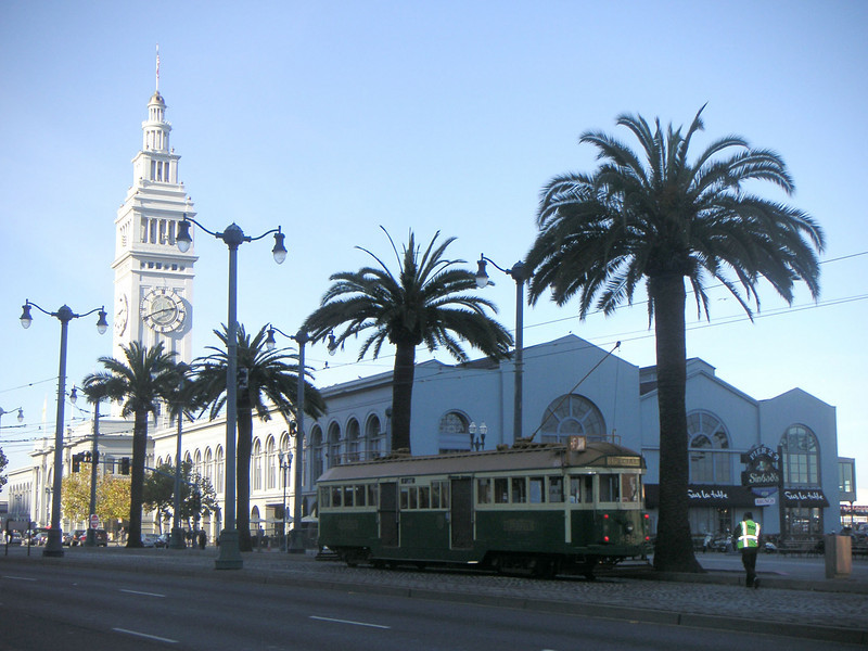 """Mature palm trees, refurbished historic street cars, and period lighting contribute to the unique sense of place created by the Ferry Building.  The <a href=""""http://www.ferrybuildingmarketplace.com/"""">Ferry Building</a>, built in 1898, has survived two major earthquakes and is listed in the National Register of Historic Places. Though it is now a major inter-modal transportation center and mixed-use complex, it has not always been so. Until the opening of the Bay and Golden Gate Bridges in 1936 and 1937, respectively, the Ferry Building was the focal point of ferry and rail transportation. When auto travel became the dominant mode for traveling across the Bay, the Ferry Building became obsolete and was transformed into primarily office use. To make matters worse, the elevated Embarcadero Freeway was built directly in front of the building in 1957 cutting the building off from the rest of downtown. The 1989 Loma Prieta Earthquake instigated the redevelopment of the Embarcadero and the Ferry Building when it destroyed part of the elevated freeway.    Two TE awards, procured in 1995 and 1998, were used to complete the Ferry Building Rehabilitation project. In total, State TE funding amounted to $2 million and generated a total local match of $2,201,000. Today, visitors and commuters from East Bay and Marin County can connect to downtown San Francisco via passenger ferries, light rail, the subway system, historic streetcars, cable cars, and buses. In addition, the Ferry Building is now truly mixed-use with retail shops, restaurants, food markets, conference center, and office space fill its historic space."""