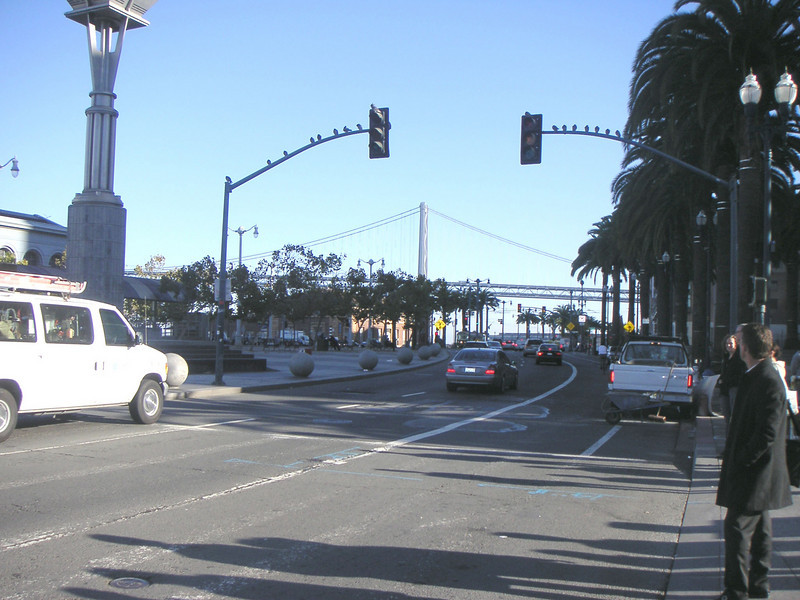 """The Bay Bridge offers a dramatic backdrop for those traveling to and from the Ferry Building.  The <a href=""""http://www.ferrybuildingmarketplace.com/"""">Ferry Building</a>, built in 1898, has survived two major earthquakes and is listed in the National Register of Historic Places. Though it is now a major inter-modal transportation center and mixed-use complex, it has not always been so. Until the opening of the Bay and Golden Gate Bridges in 1936 and 1937, respectively, the Ferry Building was the focal point of ferry and rail transportation. When auto travel became the dominant mode for traveling across the Bay, the Ferry Building became obsolete and was transformed into primarily office use. To make matters worse, the elevated Embarcadero Freeway was built directly in front of the building in 1957 cutting the building off from the rest of downtown. The 1989 Loma Prieta Earthquake instigated the redevelopment of the Embarcadero and the Ferry Building when it destroyed part of the elevated freeway.    Two TE awards, procured in 1995 and 1998, were used to complete the Ferry Building Rehabilitation project. In total, State TE funding amounted to $2 million and generated a total local match of $2,201,000. Today, visitors and commuters from East Bay and Marin County can connect to downtown San Francisco via passenger ferries, light rail, the subway system, historic streetcars, cable cars, and buses. In addition, the Ferry Building is now truly mixed-use with retail shops, restaurants, food markets, conference center, and office space fill its historic space."""