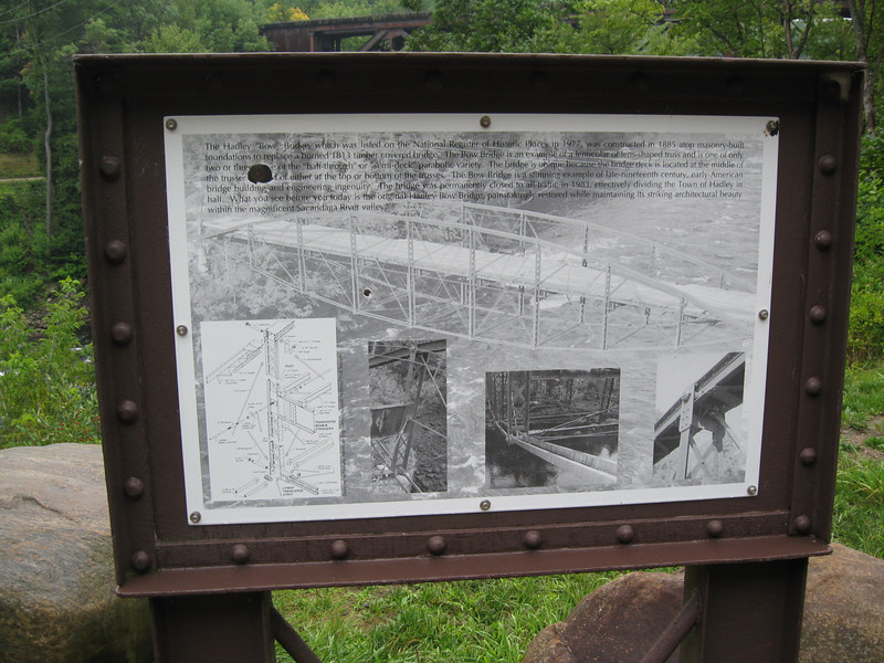 """<a href=""""http://www.flickr.com/people/dougtone/"""">Photo Courtesy of Doug Kerr</a>  Since 1813, a bridge has crossed over the Sacandaga River in the same spot that the Hadley Bow Bridge still stands. The Hadley Bow Bridge was built in 1885 on the abutments of an older bridge and served pedestrians and vehicles until 1983, when it was closed due to severe deterioration. Saratoga County had planned to dismantle the bridge but as a result of local lobbying to save the bridge, Saratoga County planned efforts to rehabilitate the bridge.  Ryan-Bigss Associates prepared a Historic Structures Report which outlined the condition and options for the bridge. When Saratoga County received a Transportation Enhancement award for $1.16 million to rehabilitate the bridge, <a href=""""http://www.ryanbiggs.com/bridges/hadley-bow-bridge/"""">Ryan-Biggs Associates</a> was selected for the category 7 project. The project included the stabilization and rehabilitation of the existing bridge and construction of an independent supports system to bring the bridges load bearing capacity up to the modern standards. The bridge is of National Historic Civil Engineering importance and was added to the National Registry of Historic Places in 1977. It provides a key link to a popular scenic vista of the Sacandaga River and nearby footpaths."""