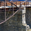 "<a href=""http://www.flickr.com/people/jeephead/"">Photo Courtesy of David Zack</a>  Since 1813, a bridge has crossed over the Sacandaga River in the same spot that the Hadley Bow Bridge still stands. The Hadley Bow Bridge was built in 1885 on the abutments of an older bridge and served pedestrians and vehicles until 1983, when it was closed due to severe deterioration. Saratoga County had planned to dismantle the bridge but as a result of local lobbying to save the bridge, Saratoga County planned efforts to rehabilitate the bridge.  Ryan-Bigss Associates prepared a Historic Structures Report which outlined the condition and options for the bridge. When Saratoga County received a Transportation Enhancement award for $1.16 million to rehabilitate the bridge, <a href=""http://www.ryanbiggs.com/bridges/hadley-bow-bridge/"">Ryan-Biggs Associates</a> was selected for the category 7 project. The project included the stabilization and rehabilitation of the existing bridge and construction of an independent supports system to bring the bridges load bearing capacity up to the modern standards. The bridge is of National Historic Civil Engineering importance and was added to the National Registry of Historic Places in 1977. It provides a key link to a popular scenic vista of the Sacandaga River and nearby footpaths."