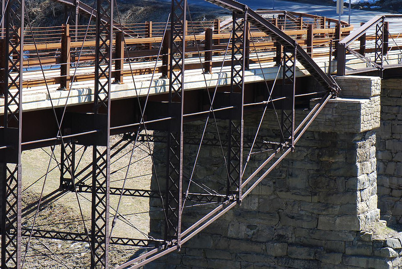 """<a href=""""http://www.flickr.com/people/jeephead/"""">Photo Courtesy of David Zack</a>  Since 1813, a bridge has crossed over the Sacandaga River in the same spot that the Hadley Bow Bridge still stands. The Hadley Bow Bridge was built in 1885 on the abutments of an older bridge and served pedestrians and vehicles until 1983, when it was closed due to severe deterioration. Saratoga County had planned to dismantle the bridge but as a result of local lobbying to save the bridge, Saratoga County planned efforts to rehabilitate the bridge.  Ryan-Bigss Associates prepared a Historic Structures Report which outlined the condition and options for the bridge. When Saratoga County received a Transportation Enhancement award for $1.16 million to rehabilitate the bridge, <a href=""""http://www.ryanbiggs.com/bridges/hadley-bow-bridge/"""">Ryan-Biggs Associates</a> was selected for the category 7 project. The project included the stabilization and rehabilitation of the existing bridge and construction of an independent supports system to bring the bridges load bearing capacity up to the modern standards. The bridge is of National Historic Civil Engineering importance and was added to the National Registry of Historic Places in 1977. It provides a key link to a popular scenic vista of the Sacandaga River and nearby footpaths."""