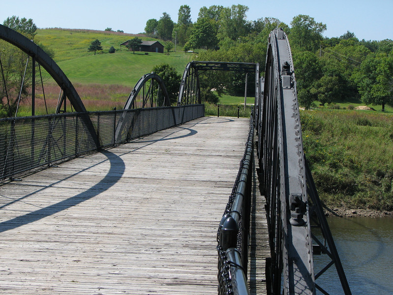 "Photo credit: Russ Coyle<br /> <br /> The Hale Bridge has helped travelers cross the Wapsipinicon River in Iowa since 1879.  Damaged by floods in 1993, the bridge was closed to traffic in 1997.  However, the bridge was nominated for the National Register of Historic Places in 1998 as the longest-standing bowstring arch bridge in Iowa.  In 2003, the bridge was moved to storage by a planning group composed of representatives from the state DOT, the Federal Highway Administration, Jones County, the Hale area, and the state historical society.  After a three-year restoration, the bridge was relocated 12 miles by air thanks to the Iowa Army National Guard, to Wapsipinicon State Park, where it serves as a pedestrian bridge.<br /> <br /> The move and the restoration were paid for in part with a Transportation Enhancements grant of $159,000.  The move was featured on the History Channel's ""Mega Movers,"" a clip of which can be viewed here: <a href=""http://www.history.com/video.do?name=science&bcpid=1681694253&bclid=1685978756&bctid=1551056441"">http://www.history.com/video.do?name=science&bcpid=1681694253&bclid=1685978756&bctid=1551056441</a>"