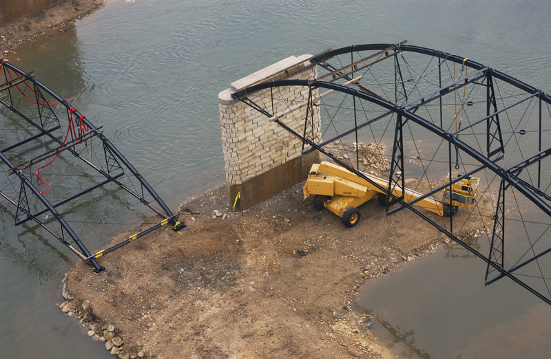 "Photo Credit: Iowa Army National Guard<br /> <br /> The Hale Bridge has helped travelers cross the Wapsipinicon River in Iowa since 1879.  Damaged by floods in 1993, the bridge was closed to traffic in 1997.  However, the bridge was nominated for the National Register of Historic Places in 1998 as the longest-standing bowstring arch bridge in Iowa.  In 2003, the bridge was moved to storage by a planning group composed of representatives from the state DOT, the Federal Highway Administration, Jones County, the Hale area, and the state historical society.  After a three-year restoration, the bridge was relocated 12 miles by air thanks to the Iowa Army National Guard, to Wapsipinicon State Park, where it serves as a pedestrian bridge.<br /> <br /> The move and the restoration were paid for in part with a Transportation Enhancements grant of $159,000.  The move was featured on the History Channel's ""Mega Movers,"" a clip of which can be viewed here: <a href=""http://www.history.com/video.do?name=science&bcpid=1681694253&bclid=1685978756&bctid=1551056441"">http://www.history.com/video.do?name=science&bcpid=1681694253&bclid=1685978756&bctid=1551056441</a>"