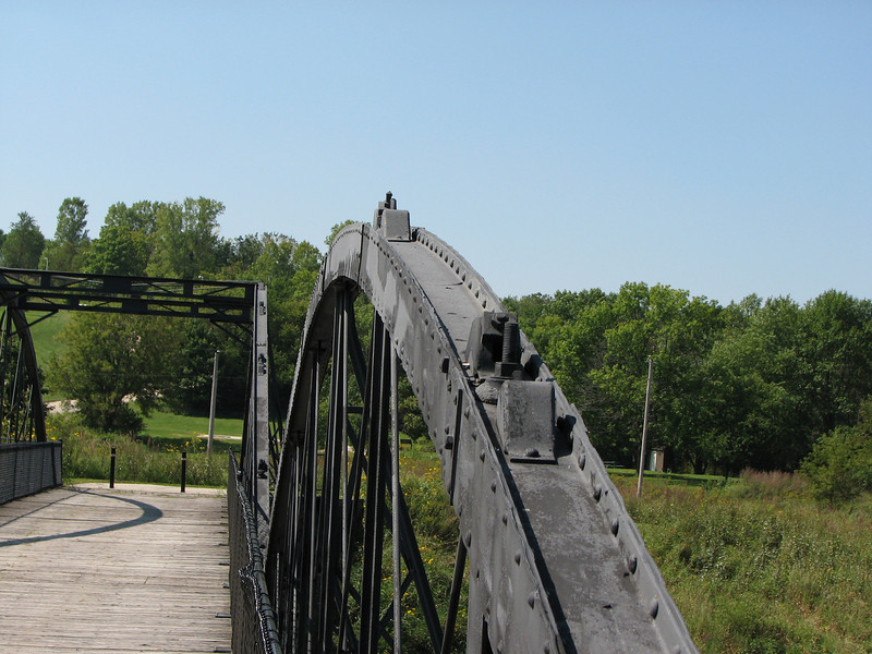 """Photo credit: Russ Coyle<br /> <br /> The historic bridge is made of wrought iron.<br /> <br /> The Hale Bridge has helped travelers cross the Wapsipinicon River in Iowa since 1879.  Damaged by floods in 1993, the bridge was closed to traffic in 1997.  However, the bridge was nominated for the National Register of Historic Places in 1998 as the longest-standing bowstring arch bridge in Iowa.  In 2003, the bridge was moved to storage by a planning group composed of representatives from the state DOT, the Federal Highway Administration, Jones County, the Hale area, and the state historical society.  After a three-year restoration, the bridge was relocated 12 miles by air thanks to the Iowa Army National Guard, to Wapsipinicon State Park, where it serves as a pedestrian bridge.<br /> <br /> The move and the restoration were paid for in part with a Transportation Enhancements grant of $159,000.  The move was featured on the History Channel's """"Mega Movers,"""" a clip of which can be viewed here: <a href=""""http://www.history.com/video.do?name=science&bcpid=1681694253&bclid=1685978756&bctid=1551056441"""">http://www.history.com/video.do?name=science&bcpid=1681694253&bclid=1685978756&bctid=1551056441</a>"""