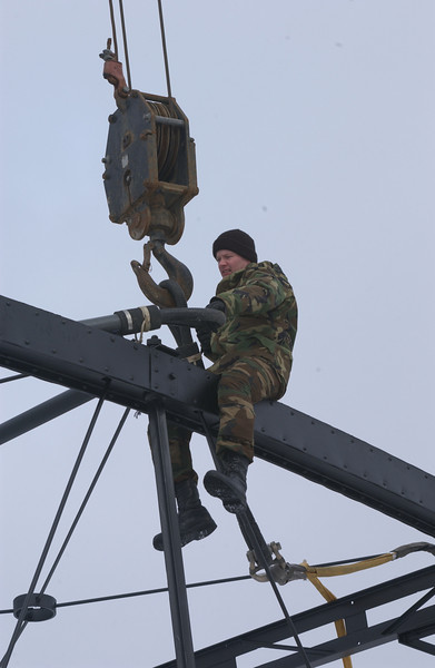 """Photo Credit: Iowa Army National Guard<br /> <br /> A Guardsman helps prepare one of the bridge spans for transport.<br /> <br /> The Hale Bridge has helped travelers cross the Wapsipinicon River in Iowa since 1879.  Damaged by floods in 1993, the bridge was closed to traffic in 1997.  However, the bridge was nominated for the National Register of Historic Places in 1998 as the longest-standing bowstring arch bridge in Iowa.  In 2003, the bridge was moved to storage by a planning group composed of representatives from the state DOT, the Federal Highway Administration, Jones County, the Hale area, and the state historical society.  After a three-year restoration, the bridge was relocated 12 miles by air thanks to the Iowa Army National Guard, to Wapsipinicon State Park, where it serves as a pedestrian bridge.<br /> <br /> The move and the restoration were paid for in part with a Transportation Enhancements grant of $159,000.  The move was featured on the History Channel's """"Mega Movers,"""" a clip of which can be viewed here: <a href=""""http://www.history.com/video.do?name=science&bcpid=1681694253&bclid=1685978756&bctid=1551056441"""">http://www.history.com/video.do?name=science&bcpid=1681694253&bclid=1685978756&bctid=1551056441</a>"""