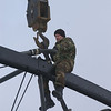 "Photo Credit: Iowa Army National Guard<br /> <br /> A Guardsman helps prepare one of the bridge spans for transport.<br /> <br /> The Hale Bridge has helped travelers cross the Wapsipinicon River in Iowa since 1879.  Damaged by floods in 1993, the bridge was closed to traffic in 1997.  However, the bridge was nominated for the National Register of Historic Places in 1998 as the longest-standing bowstring arch bridge in Iowa.  In 2003, the bridge was moved to storage by a planning group composed of representatives from the state DOT, the Federal Highway Administration, Jones County, the Hale area, and the state historical society.  After a three-year restoration, the bridge was relocated 12 miles by air thanks to the Iowa Army National Guard, to Wapsipinicon State Park, where it serves as a pedestrian bridge.<br /> <br /> The move and the restoration were paid for in part with a Transportation Enhancements grant of $159,000.  The move was featured on the History Channel's ""Mega Movers,"" a clip of which can be viewed here: <a href=""http://www.history.com/video.do?name=science&bcpid=1681694253&bclid=1685978756&bctid=1551056441"">http://www.history.com/video.do?name=science&bcpid=1681694253&bclid=1685978756&bctid=1551056441</a>"